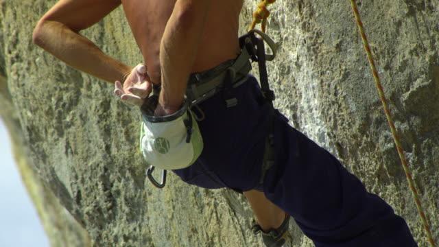 cu man climbing rock facerock face, dipping hand in chalk-bag and ascending / krabi, thailand - tragetasche oder tragebeutel stock-videos und b-roll-filmmaterial