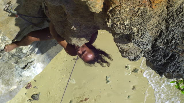 ms man climbing rock facewith bare feet, beach and sea in background / krabi, thailand - hex climbing equipment stock videos and b-roll footage