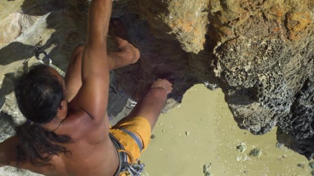 ms cu man climbing rock facewith bare feet, beach and sea in background, clipping rope into karabiner and ascending / krabi, thailand - hex climbing equipment stock videos and b-roll footage