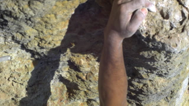 ecu man climbing rock facewith bare feet, beach and sea in background, dipping hand into chalk-bag and ascending / krabi, thailand - beach bag stock videos and b-roll footage