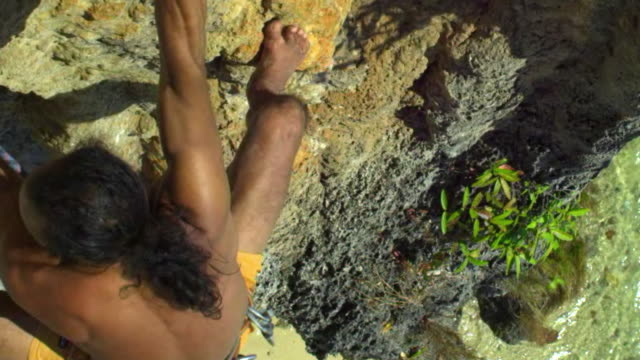 cu man climbing rock facewith barefoot, dipping hand into chalk-bag and ascending, clipping rope into karabiner / krabi, thailand - hex climbing equipment stock videos and b-roll footage