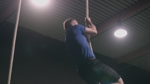 Man climbing rope in a gym
