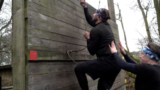Man climbing rope wall on Assault Course / Obstacle course - Slow Motion