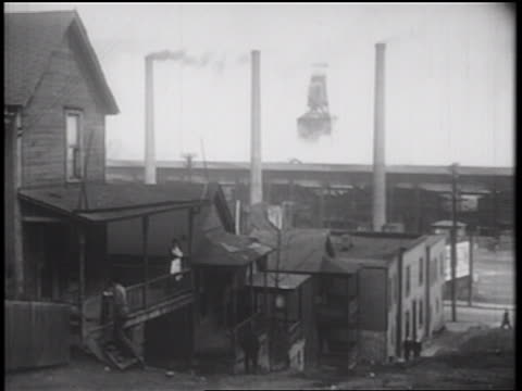 stockvideo's en b-roll-footage met b/w 1939 man climbing stairs to balcony of apartment in slums / smokestacks in background / documentary - grote depressie nieuwsevenement