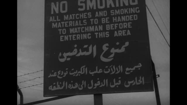 man climbing stairs toward top of storage tank in fg, looking down line of tanks / storage tank with man walking in front / looking down oil... - no smoking sign stock videos & royalty-free footage