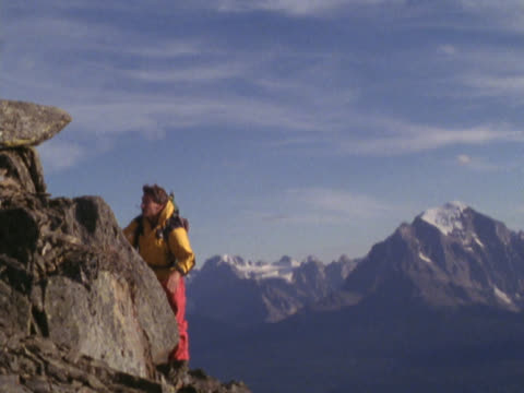 man climbing to top of mountain peak - mpeg videoformat stock-videos und b-roll-filmmaterial