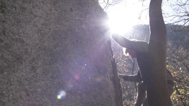 stockvideo's en b-roll-footage met man climbing up a boulder reaching the top - boulder rock