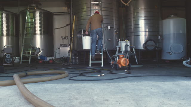 ws man climbing up ladder in tank room of winery / zillah, washington, usa        - storage tank stock videos & royalty-free footage