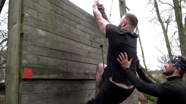Man climbing up rope wall on Assault Course / Obstacle course - Slow Motion