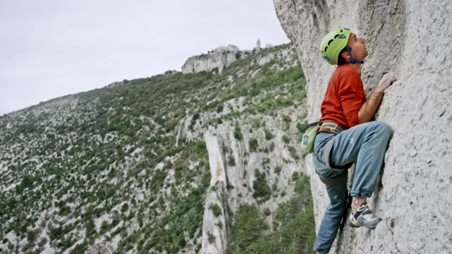 man climbing up the cliff - rock climbing stock videos & royalty-free footage