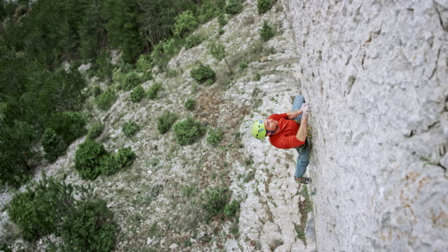 man climbing up the cliff with the help of a belay partner - belaying stock videos & royalty-free footage