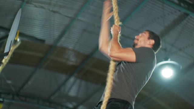 MS A man climbs a rope in a gym / Rio de Janeiro, Brazil