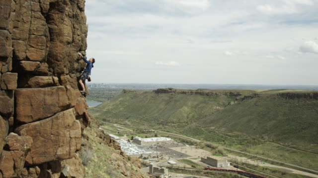 man climbs a steep rock face with the city of denver in the background - wide stock-videos und b-roll-filmmaterial