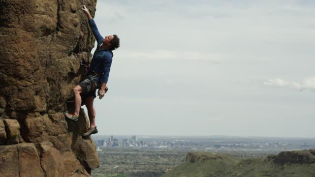 vidéos et rushes de man climbs a steep rock  facewith the city of denver in the background - lutte concepts