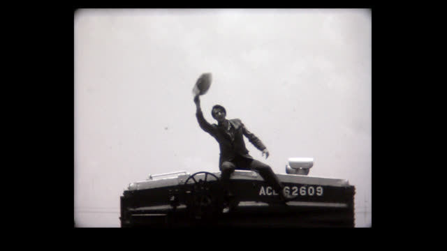stockvideo's en b-roll-footage met 1968 man climbs atop train car and waves wildly - waving