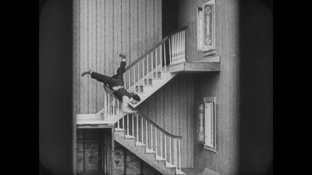 1920 man (buster keaton) climbs in window to embrace woman is caught escaping by angry father - sliding stock videos & royalty-free footage