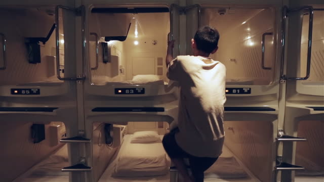 ws a man climbs into a capsule room in a capsule hotel and lies down / tokyo, japan - ヤングアダルト点の映像素材/bロール