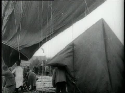 vídeos de stock e filmes b-roll de a man climbs into a round vessel attached to a large hot air balloon. - preto e branco