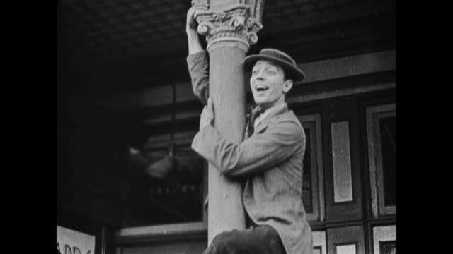 1917 man (buster keaton) climbs lamppost at coney island to watch parade, but falls when he claps his hands - 無声映画点の映像素材/bロール
