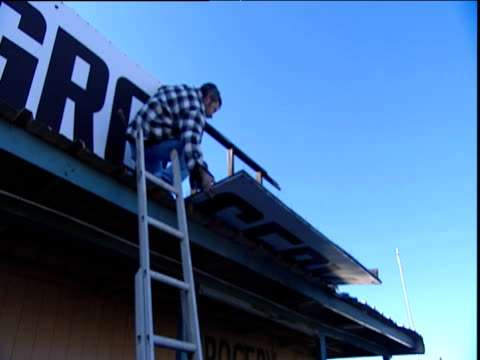 vidéos et rushes de man climbs last rungs of ladder scales roof of roadside convenience store and fixes shop sign arizona usa - store