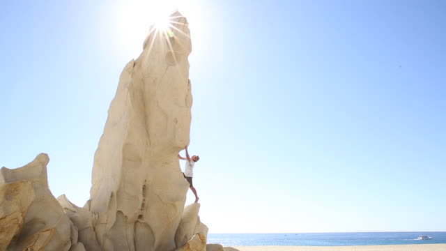 man climbs on granite pinnacle above beach, ocean behind - one mature man only stock videos & royalty-free footage