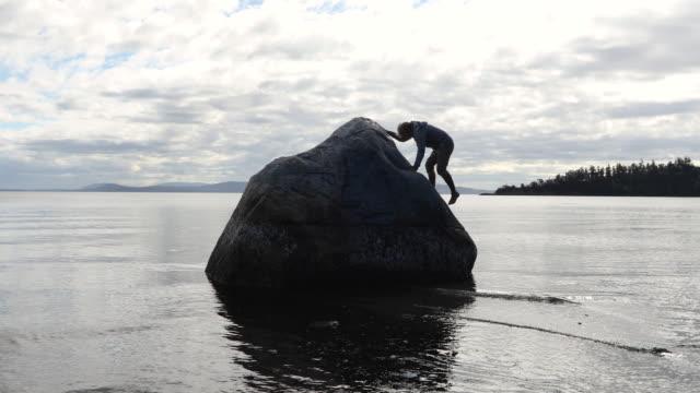 Man klättrar klippa ovanför grunt hav, vid soluppgången