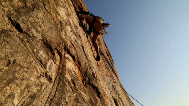 man climbs sheer rock face above belayer - rock face stock videos & royalty-free footage