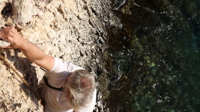 Man climbs sheer rock face above sea, wearing camera
