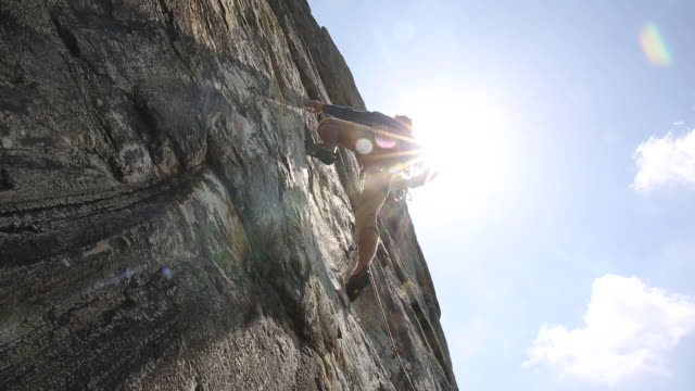 man climbs sheer rock face into sunlight, above protection - rock face stock videos & royalty-free footage