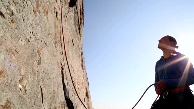 man climbs sheer rock face while teammate belays - rock face stock videos & royalty-free footage