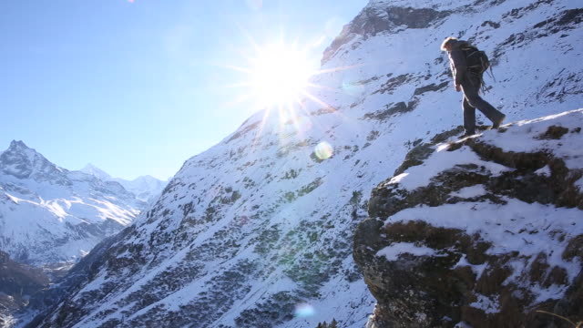 Man climbs to mountain summit, looks out to sunrise
