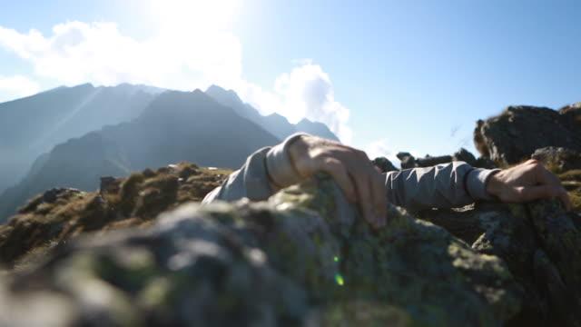 Man climbs to rock crest sun sets behind mountain range