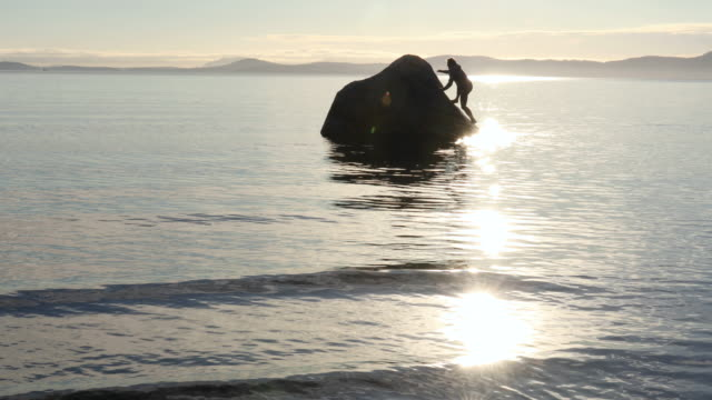 Man climbs to summit of rock above calm sea