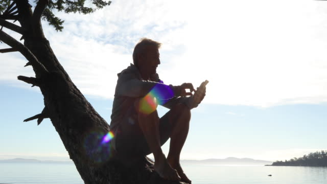 Man climbs tree trunk and relaxes with smart phone
