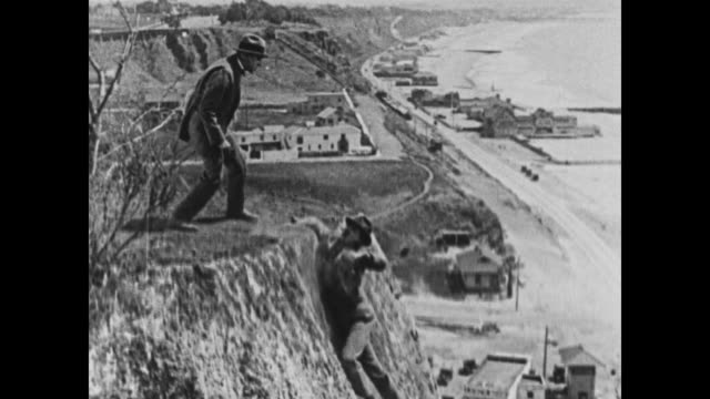 1924 man clings to cliff edge as other man stamps on his hands, he gets his grip and retaliates - gripping stock videos and b-roll footage