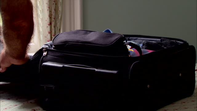 a man closes his packed carry-on suitcase then zips it. - packing stock videos & royalty-free footage