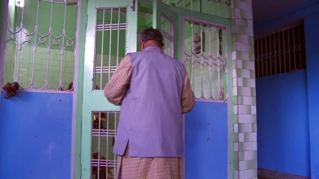 man closing and locking hindu temple doors  - dhoti video stock e b–roll