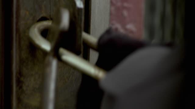 ECU TU Man closing and opening padlock on door, Brooklyn, New York City, New York State, USA