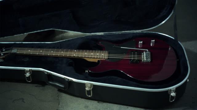 cu man closing guitar case, low section - 中年の男性一人点の映像素材/bロール