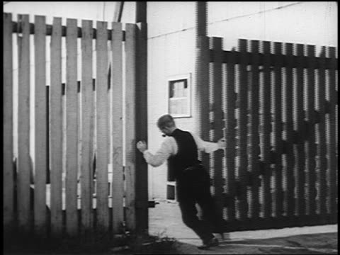 vídeos y material grabado en eventos de stock de view man closing wooden gate of factory during great depression - 1936