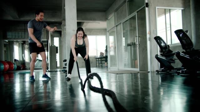 Man coaching asian woman on ropes gym exercise