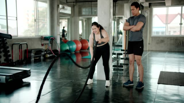 man coaching asian woman on ropes gym exercise - crouching stock videos & royalty-free footage