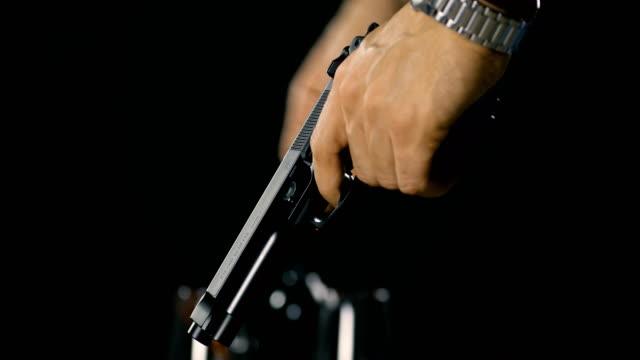 vídeos de stock e filmes b-roll de man cocking a gun preparing to fire - guardar