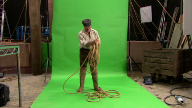 a man coils up a rope as he stands in front of a green-screen in a warehouse. - rope stock videos & royalty-free footage