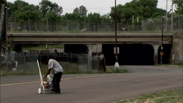 A man collects trash near a dilapidated building. Available in HD.