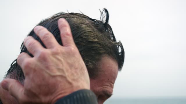 vídeos de stock, filmes e b-roll de man combing hair - diving suit
