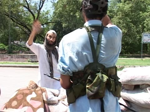 man comes to chat with an armed man standing behind a sandbag wall during the attacks of the red mosque of july 2007 - sandbag stock videos and b-roll footage