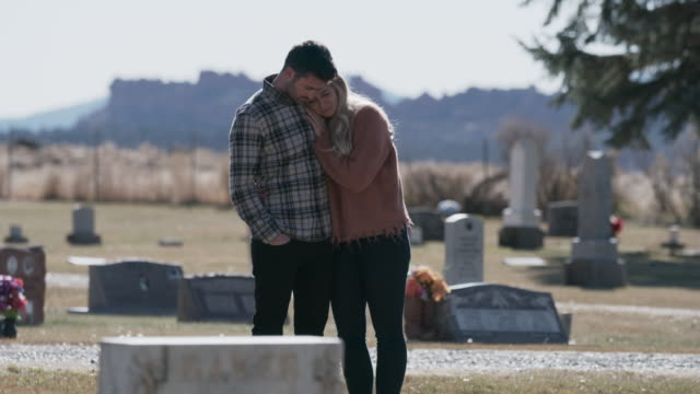 man comforting woman near gravestone in cemetery / bicknell, utah, united states - grief stock videos & royalty-free footage