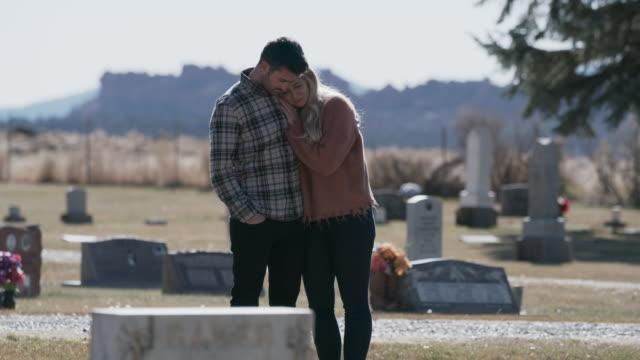 Man comforting woman near gravestone in cemetery / Bicknell, Utah, United States