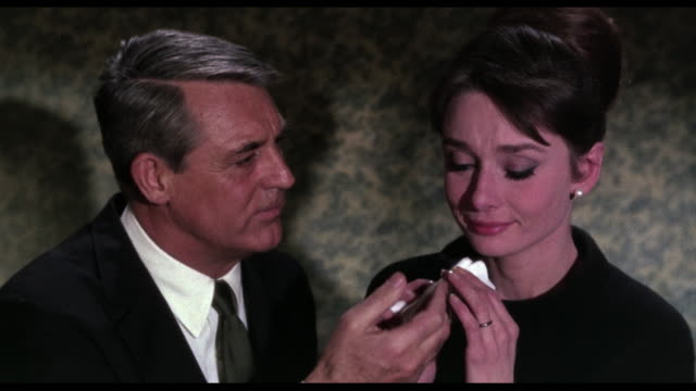 1963 Man (Cary Grant) comforts crying woman (Audrey Hepburn) before the telephone buzzes